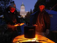 Occupy protesters warm their hands while brewing coffee on a fire pit at their encampment across from the State House in Augusta, Maine.