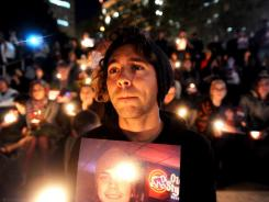Zachary Greer holds a photo of Scott Olsen during a candlelight vigil on Thursday in Oakland, Calif.