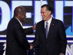 Businessman Herman Cain greets former Massachusetts governor Mitt Romney before a Republican presidential debate on Oct. 18 in Las Vegas.