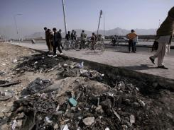 Afghans gather at the site of Saturday's suicide car bombing in Kabul.