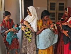 Indian women hold their newborn babies as they wait for checkups in Allahabad, which is in India's most populous state of Uttar Pradesh.
