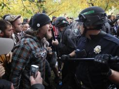 "Police officers in riot gear face off with demonstrators at the ""Occupy Denver"" camp Saturday."