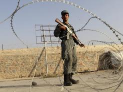An Afghan police officer stands guard at a checkpoint next to the site of a suicide bombing in Kandahar, Afghanistan, on Monday.