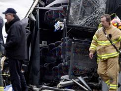 Emergency personnel attend to the crash of a low-fare Chinatown bus on March 12.