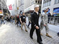 Military veterans march past the New York Stock Exchange on Wednesday in New York.