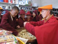Ye Liping, right, sells rolls at a store at the remote Larung Gar Buddhist Institute in Serthar. Two years ago, Ye left his business and family for the monastic hardships of life at Larung Gar.