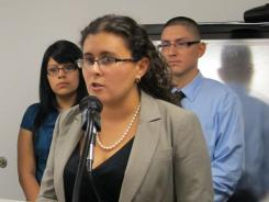 Southern Poverty Law Center attorney Miriam Haskell announces a lawsuit Oct. 19 on behalf of five U.S.-born students, including Kassandra Romero, left, and Noel Saucedo.