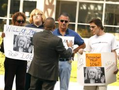 State Sen. Steve Gallardo, with his back to the camera, talks with protesters Tuesday in Phoenix.