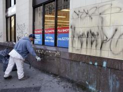 Cleaners remove graffiti off of a Rite Aid store in Oakland, Calif., on Thursday, after a massive anti-Wall Street protest turned violent and chaotic the night before.