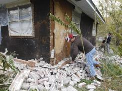 Chad Devereaux picks up bricks that fell from his in-laws' home in Sparks, Okla., on Sunday.