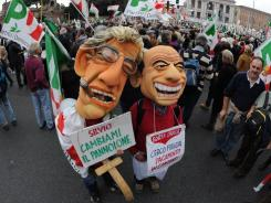 Demonstrators wear masks of Italian Prime Minister Silvio Berlusconi, right, and the leader of the Northern League, Umberto Bossi, during a Saturday protest in Rome.
