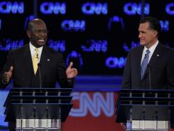 Businessman Herman Cain and former Massachusetts governor Mitt Romney participate in a debate on Oct. 18 in Las Vegas.