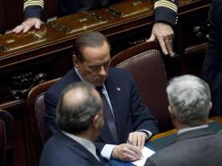 Italian Premier Silvio Berlusoni writes a note at the end of a voting session Tuesday at the lower chamber in Rome.