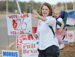 Joyce Haskins, with her grandchild Landry Bruce, waves outside the voting booths at the Oxford Conference Center in Oxford, Miss.