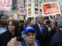 New York City Council Member Jumaane D. Williams, left, and New York State Assemblyman Jeffrion Aubry, right, join Occupy Wall Street protesters marching to Zuccotti Park on Monday. A small group of activists plans to leave the park on Wednesday to march to Washington.