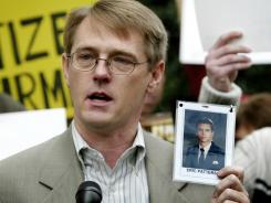 David Clohessy, director of the Survivors Network of those Abused by Priests, holds up a photo of Eric Patterson, who killed himself after revelations of his alleged abuse by a priest, during a 2002 news conference.