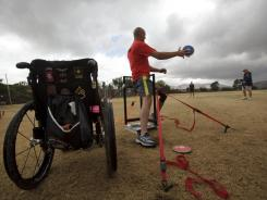 A former army sergeant throws a discus in front of his wheelchair as he takes part in the Paralympic Military Sports Camp.