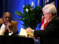 Republican presidential candidate Herman Cain, left, pauses before responding to a question from fellow candidate Newt Gingrich during a debate Nov. 5 in The Woodlands, Texas.