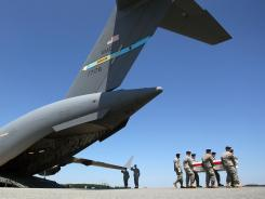 An Army team moves a transfer case during a dignified transfer at Dover Air Force Base.