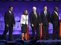 Rick Santorum, Michele Bachmann, Newt Gingrich, Mitt Romney, Herman Cain, Rick Perry, Ron Paul and Jon Huntsman stand on stage Wednesday before a debate at Oakland University in Auburn Hills, Mich.