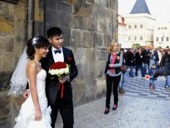 Newlyweds pose in Prague's Old Town Square after their marriage on Friday, Nov. 11, 2011. Thousands of couples from around the world have chosen the date of 11/11/11 to be married due to its symbolism.