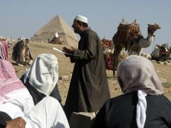 Egyptian camel handlers attend Friday prayers at the Giza Pyramids in Cairo.