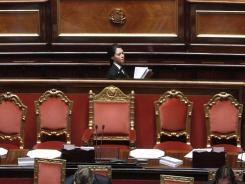 A worker of the Italian Senate walks past the empty chair of Italian Premier Silvio Berlusconi on Friday during a voting session on economic reform measures demanded by the European Union.