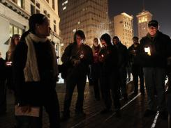 Demonstrators light candles in remembrance of a man who was shot and killed Thursday outside a camp site for Occupy protesters at Frank Ogawa Plaza in Oakland.