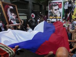 Pro-Syrian regime protesters demonstrate against the Arab League decision to suspend Syria in front of the Syrian embassy in Beirut.