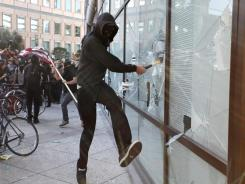 A masked Occupy Oakland protester smashes a window at a Wells Fargo Bank branch on Nov. 2.