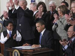 President Obama is applauded after signing the health care bill into law at the White House on March 23, 2010. On Monday, the Supreme Court announced it would hear a case on the law's constitutionality.