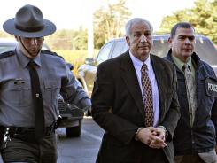 Former Penn State football defensive coordinator Jerry Sandusky is escorted by Pennsylvania State Police and Attorney General's Office officials on  Nov. 5.