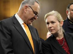 U.S. Sen. Kirsten Gillibrand, D-N.Y., listens to Sen. Charles Schumer, D-N.Y., during a news conference on Tuesday on Capitol Hill.