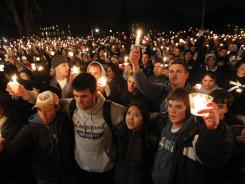 In support of the victims:  People hold a candlelight vigil last Friday in front of the Old Main building on the Penn State campus in State College, Pa.