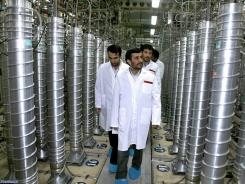 Iran leader Mahmoud Ahmadinejad, front, at the Natanz Uranium Enrichment Facility. Foreign policy analysts say political pressure is hurting Iran's commerce.