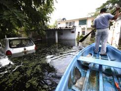 A man makes his way on a boat in a flooded area in Tabasco, Mexico, on Oct. 23.
