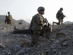 American troops observe a patrol of U.S. Army and Afghan National Army soldiers and Afghan police on Oct. 3 in Afghanistan. The U.S. Army reduced mefloquine prescriptions for soldiers sent to malaria-prone Afghanistan.