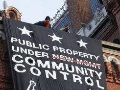 A group of protesters inspired by Occupy D.C. look out from the roof after hanging a banner on Franklin School building, in Washington on Saturday.