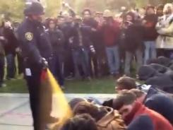 In this image made from video, a police officer uses pepper spray as he walks down a line of Occupy demonstrators sitting on the ground at the University of California, Davis on Friday.