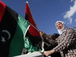 A woman waves a pre-Gadhafi flag during a celebration of the capture of Seif al-Islam Gadhafi in Tripoli.