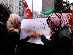 "Syrians living in Turkey write ""Freedom"" with their blood during a Friday protest against the government of Syria's President Bashar al-Assad in front of the Syrian consulate in Istanbul."