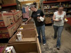 Dixie Care and Share volunteers Krissie Wilcox, left, and Paige Martin load up boxes of food for people in need.