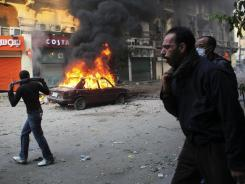Protesters move away from tear gas fired by Egyptian riot police during clashes near Tahrir Square on Monday in Cairo, Egypt.