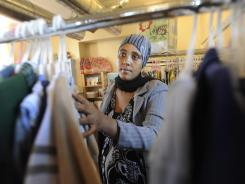 Basha Badada looks for sizes to fit her son, Abdalla, 1, at the Teddy Bear Den.