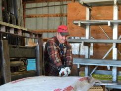Ken Reeve cuts the straps off a pack of sheet metal roofing at a company in Fort Collins, Colo.