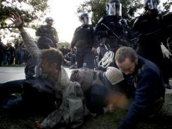 Occupy UC Davis protesters react after being pepper sprayed by police who came to remove tents on the school's quad Friday in Davis, Calif.