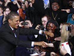 Vows to plow ahead with cuts:  President Obama greets audience members Tuesday before a jobs speech in Manchester, N.H.