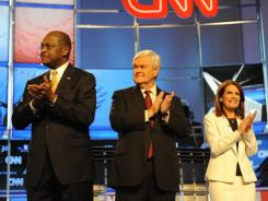In the spotlight: Republican presidential candidates include Herman Cain, Newt Gingrich and Rep. Michele Bachmann applaud before Tuesday night's debate begins at Constitution Hall in Washington. Much of the attention was focused on Gingrich.