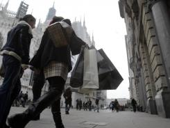 Two women walk past the Milan gothic cathedral in Italy on Tuesday.
