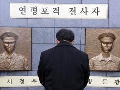 A man pays a silent tribute in front of two bust sculptures of two killed marines during a memorial service on Yeonpyeong Island, South Korea.
